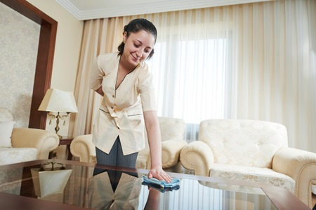Hotel service. female housekeeping worker with cleaning table from dust in room photo