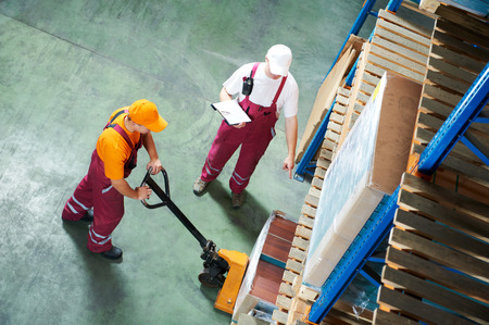 workers with fork pallet truck stacker in warehouse loading furniture panels photo