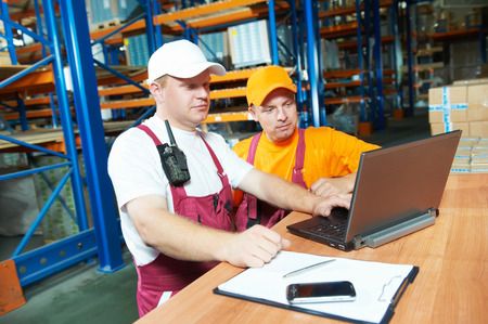 two young workers man in uniform in front of warehouse rack arrangement stillages using notebook computer photo