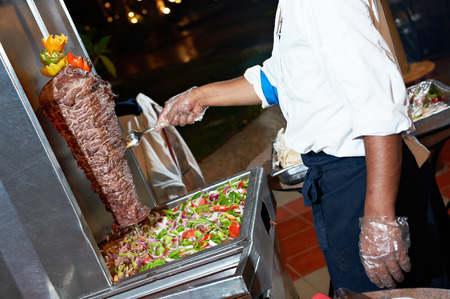 Arab chef in cook uniform making kebab with meat and vegetables photo