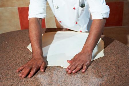 hand of chef baker in white uniform making pizza at kitchen photo