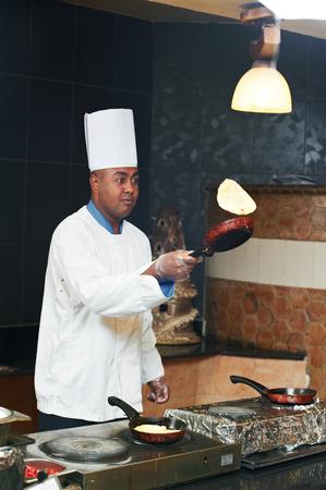 arab chef baker in white uniform frying pancake at kitchen photo