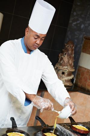 arab chef baker in white uniform frying omelette or pancake at kitchen photo