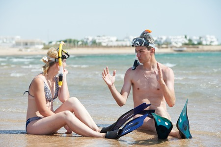 Young couple with snorkel gear sharing impressions on red sea beach at vacations photo