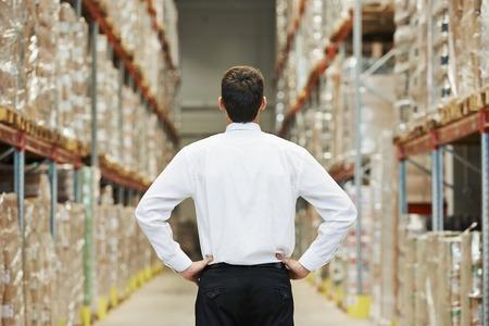 ビューアーに向かって後ろに大きな近代的な倉庫に立っている男性マネージャー男 写真素材
