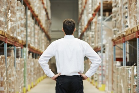 warehouse equipment: male manager man standing in big modern warehouse with back towards viewer Stock Photo