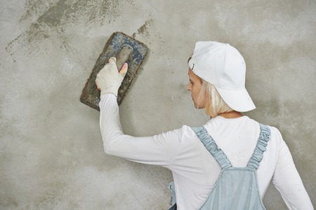 Plasterer at indoor wall renovation decoration with float and plaster Stock Photo
