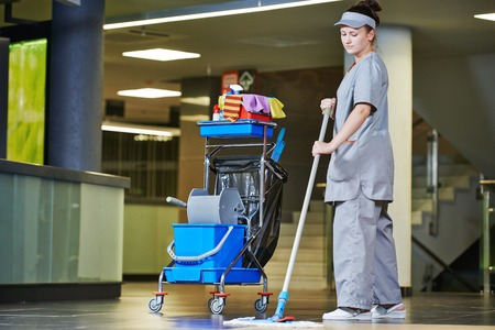 charwoman: female cleaner with mop and uniform cleaning hall floor of public business building
