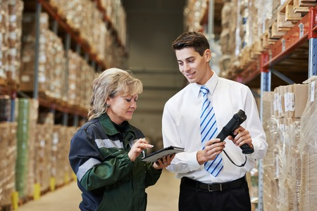 manager and worker in warehouse with bar code scanner photo