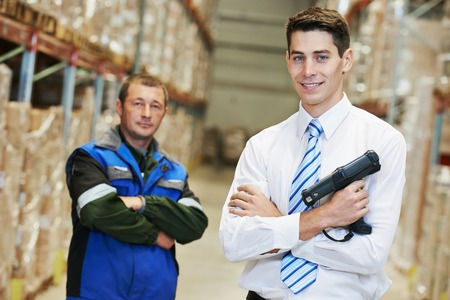 smiling manager and worker in warehouse with bar code scanner photo