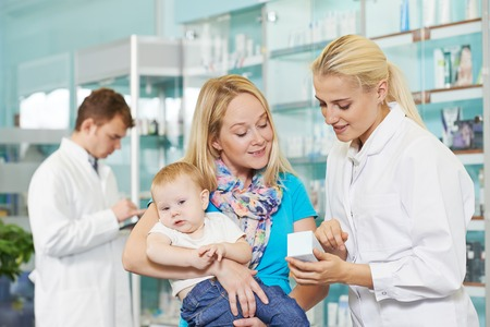 pharmacy store: Cheerful pharmacist chemist woman giving vitamins to child girl in pharmacy drugstore Stock Photo