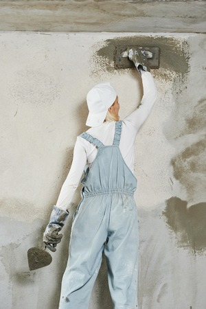 Plasterer at indoor wall renovation decoration with float and plaster photo
