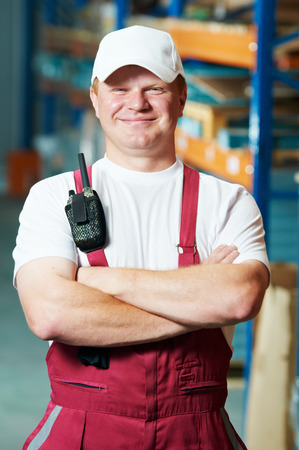 young warehouse worker portrait in uniform in front of modern storehouse shelves photo