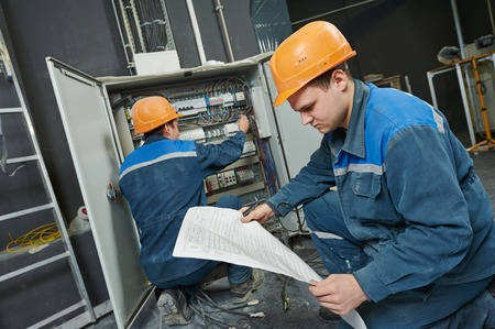 two electrician builder engineer with blue print scheme project in front of fuse switch box photo