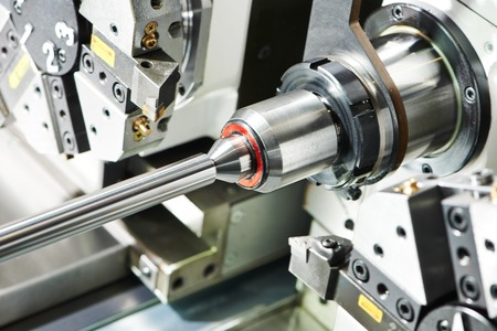 machine: shaft detail turning on metal cutting machine tool at manufacturing factory Stock Photo