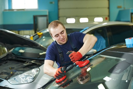 Automobile glazier adding glue on windscreen or windshield of a car in auto service station garage before installation Banque d'images