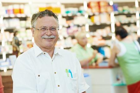 clothing stores: smiling male pharmacist chemist man portrait in pharmacy drugstore Stock Photo