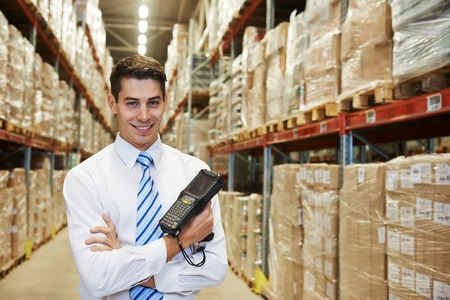 smiling manager in warehouse with bar code scanner Banque d'images