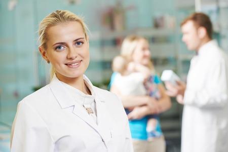 medical services: cheerful female pharmacist chemist woman portrait in pharmacy drugstore