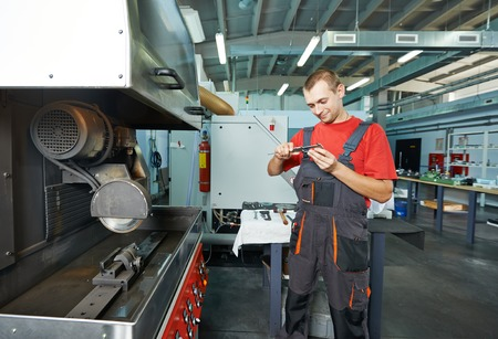 manufacture technician worker with micrometer at factory metal machining shop photo