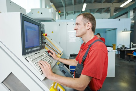 machining center: manufacture technician worker operating metal machining center at factory shop Stock Photo