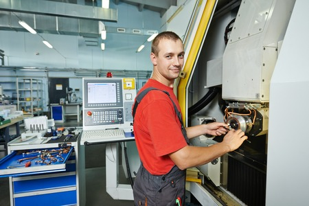 manufacture worker operating metal machining center at factory shop photo