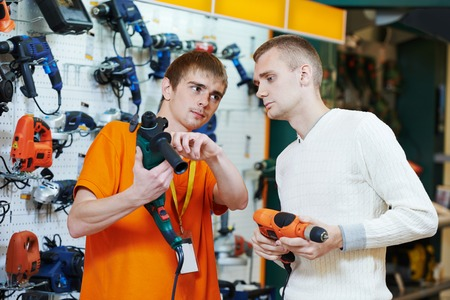Sale assistant demonstrating electric drill perforator to young man in electrical appliance shopping mall supermarket photo
