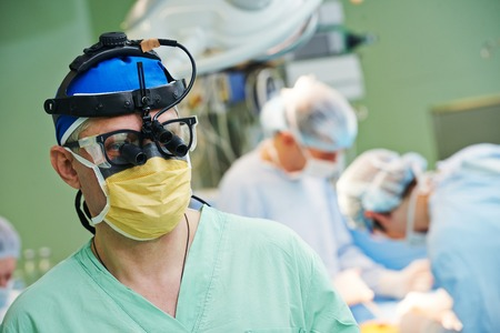 cardiosurgery: surgeon in uniform at heart transplantation operation on a patient at cardiac surgery clinic