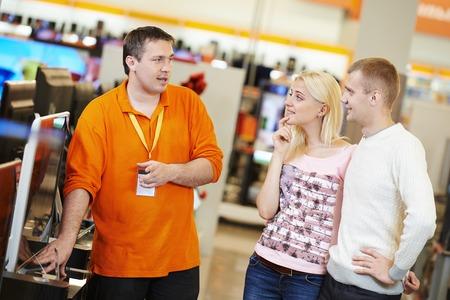 Giovane famiglia scegliendo televisore con assistente di negozio in home appliance centro commerciale supermercato