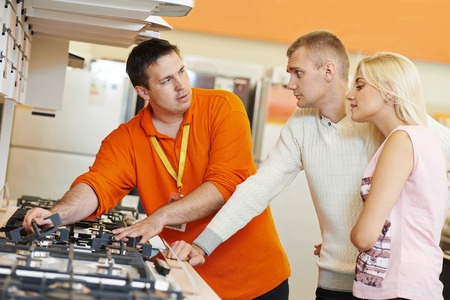 home stores: Sale assistant demonstrating cooker stove to young family in home appliance shopping mall supermarket Stock Photo