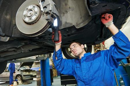 automonteur onderzoeken autowiel remschijf en schoenen van opgeheven auto bij reparatie tankstation