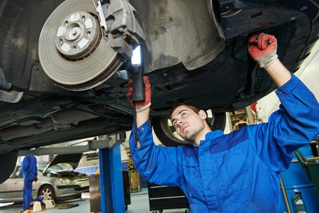 mecánico de automóviles examinar rueda de disco y los zapatos de automóvil levantado freno del coche en la estación de servicio de reparación Foto de archivo