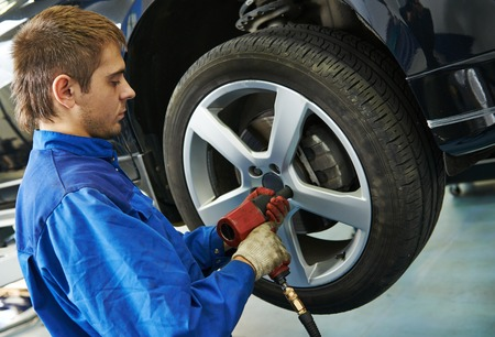 pneumatic tyres: car mechanic screwing or unscrewing car wheel of lifted automobile by pneumatic wrench at repair service station