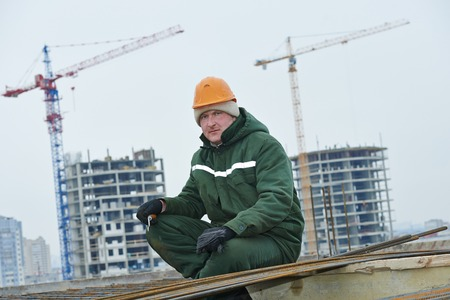 builder worker knitting metal rods bars into framework reinforcement for concrete pouring at construction site photo