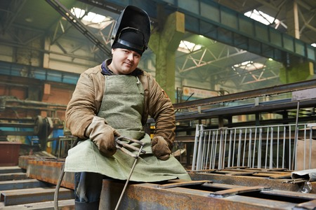 electrode: welder with electrode at arc welding in manufacture production plant Stock Photo