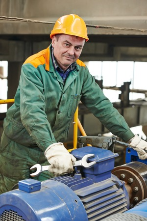 metal processing: smiling industrial worker with spanner at factory workshop Stock Photo