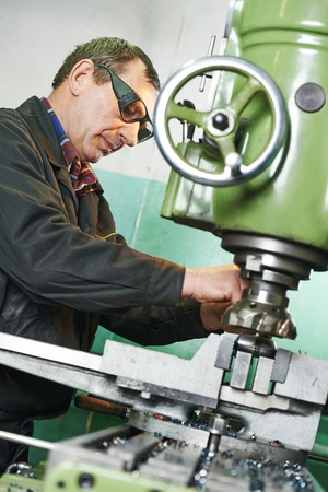 manufacturing equipment: milling machine operator working in factory workshop