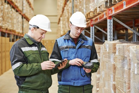 workers in warehouse with bar code scanner and tablet computer