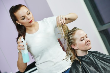 hairtician: hairdresser stylinghair with hairspray of woman client at beauty parlour after highlighting