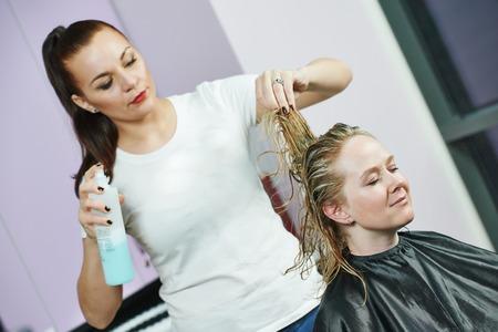 tinte cabello: stylinghair peluquero con la laca de pelo del cliente de la mujer en el salón de belleza después de resaltar Foto de archivo