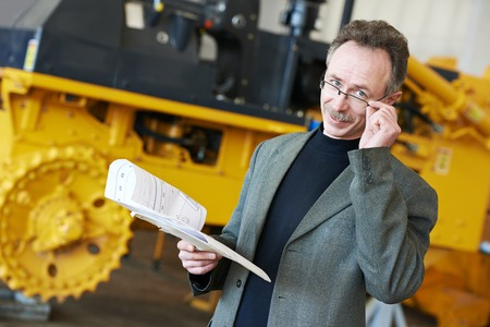technologist: industrial engineer manager with technical drawing at heavy industry machinery assembling on production manufacturing factory line
