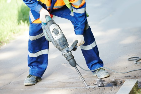 asphalting: Builder worker with pneumatic hammer drill equipment breaking asphalt at road construction site