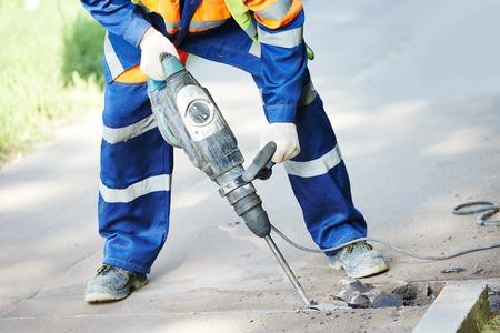 constructor: Trabajador del constructor con el neum�tico equipo de perforaci�n martillo rompiendo el asfalto en el sitio de la construcci�n de carreteras