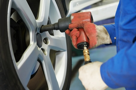 motor mechanic: car mechanic screwing or unscrewing car wheel of lifted automobile at repair service station