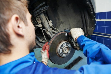 disassembly: car mechanic examining car wheel brake disc and shoes of lifted automobile at repair service station