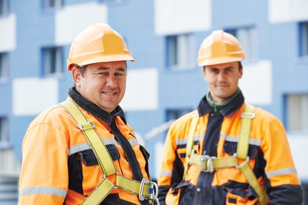 job site: Team of smiling facade builders workers in protective uniform at construction building site