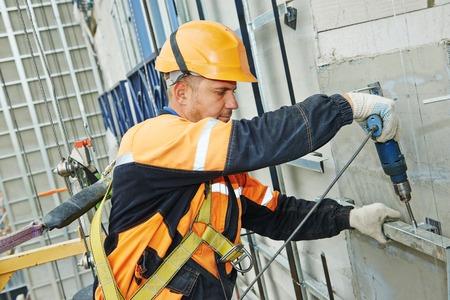 taladro: Constructor del trabajador de hacer la construcción para la ventilación de fachada de un edificio con el taladro destornillador