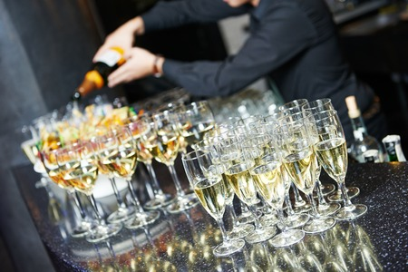 Waiter bartender pouring white wine into glasses at party event photo