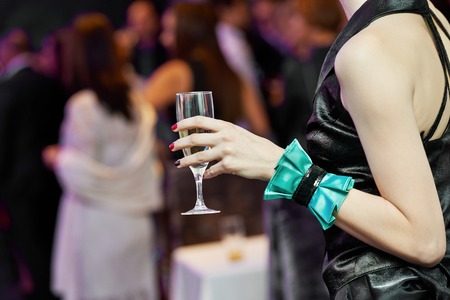 Female woman guest hand and glass with wine at party photo