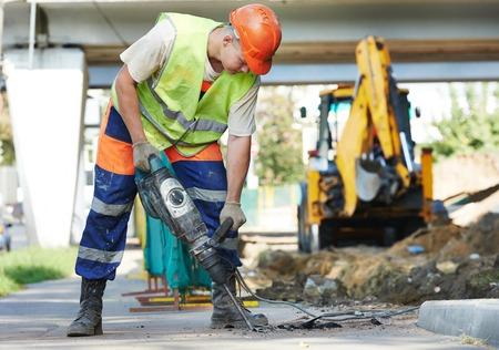 Trabajador del constructor con el neumático equipo de perforación martillo rompiendo el asfalto en el sitio de la construcción de carreteras